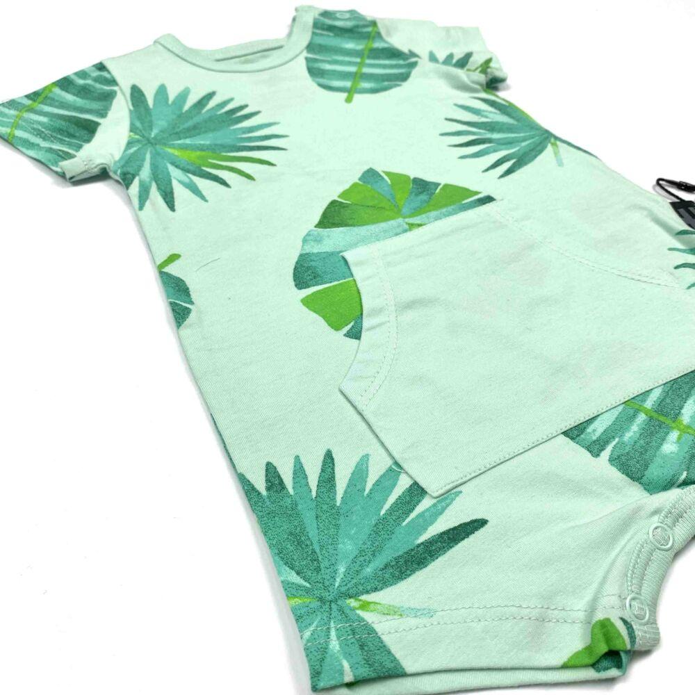 Kisfiú nyári napozó zöld alpon levél mintával közeli.